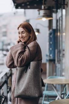Donna attraente in trench sulla strada della città