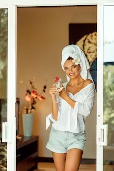 Donna attraente in un accappatoio bianco e asciugamano tenendo il bicchiere di champagne e sorridendo alla telecamera. spa e resort