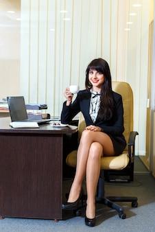 Donna attraente in una gonna corta che beve caffè nell'ufficio