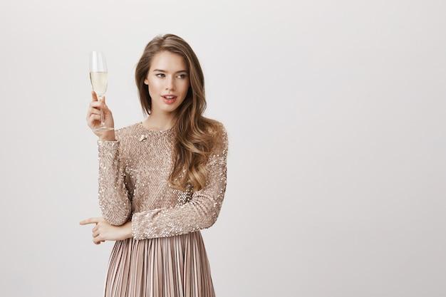 Donna attraente in vestito da sera che tiene vetro di champagne
