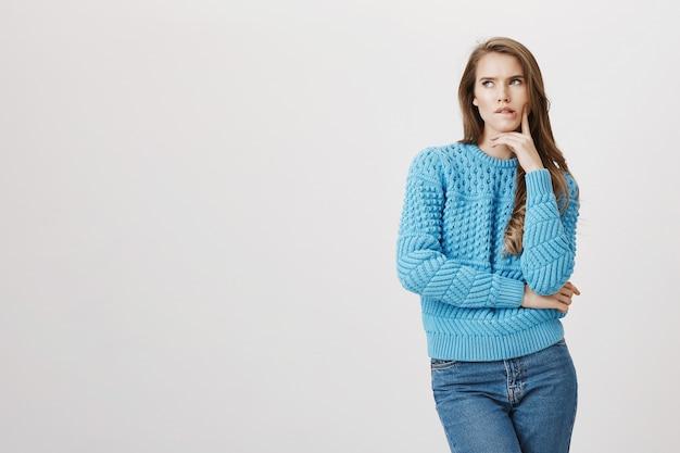 Donna attraente nel maglione che pensa, labbro mordace premuroso