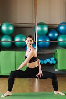 Donna attraente sorridente che si esercita sulla stuoia verde nel centro di forma fisica