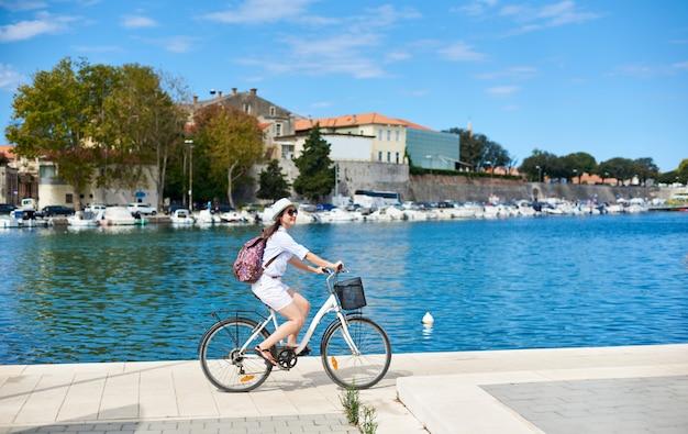 Donna attraente sorridente con lo zaino che guida una bici lungo il marciapiede pietroso dall'acqua blu del porto accogliente e dai cottage della località di soggiorno sulla riva opposta del lago. concetto di turismo e vacanze.