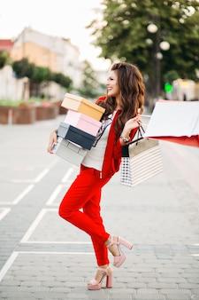 Donna attraente sorridente in scatole di scarpe eleganti della tenuta del vestito di sport rosso e sacchetti della spesa nella via.