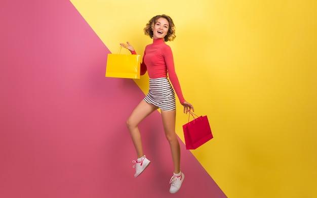Donna attraente sorridente in vestito colorato alla moda che salta con le borse della spesa