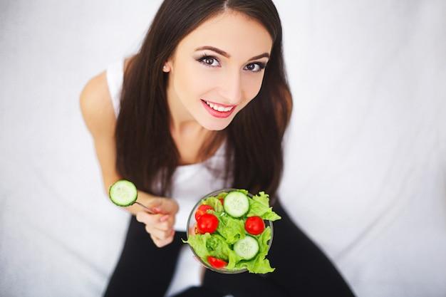 Donna attraente sorridente sportiva che mangia pranzo vegetariano alla cucina