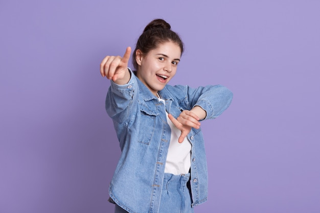 Donna attraente spensierata che guarda e che indica e che sta isolata sopra la parete lilla, indossando la giacca di jeans alla moda e la camicia bianca, donna castana con il nodo.