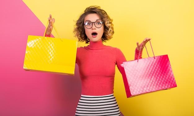 Donna attraente uscita in abito colorato elegante che tiene le borse della spesa con espressione del viso sorpreso, emozione divertente, sfondo rosa giallo, collo a polo, minigonna a righe, saldi, discout, shopaholic