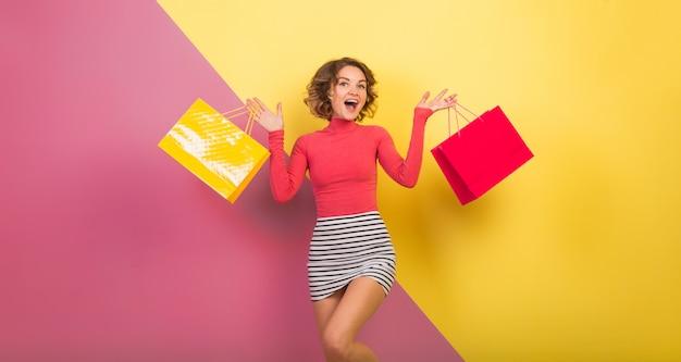 Donna attraente uscita in vestito colorato alla moda che tiene i sacchetti della spesa con l'espressione del viso sorpreso