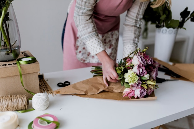 Donna avvolgendo e organizzando bouquet