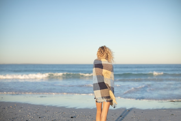 Donna avvolta in una coperta in piedi sulla spiaggia