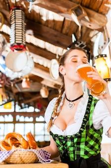Donna bavarese che beve birra di grano