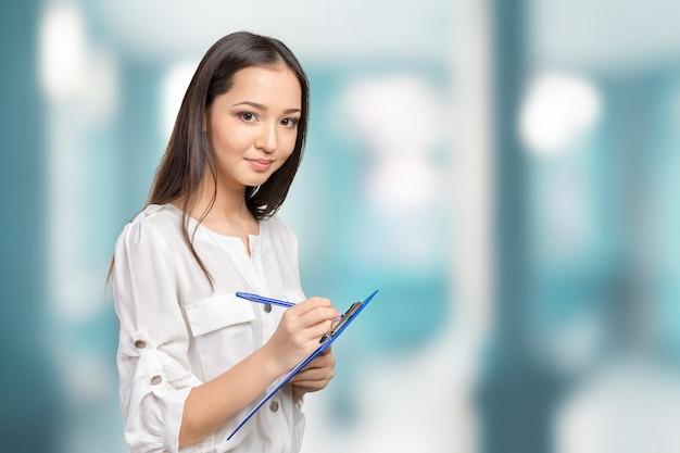 Donna bella business prendendo appunti sulla sua lavagna per appunti