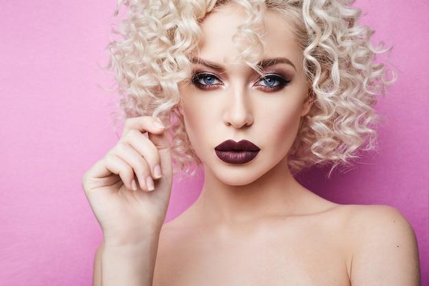 Donna bella e alla moda con incredibili occhi azzurri, capelli biondi ricci e trucco professionale brillante