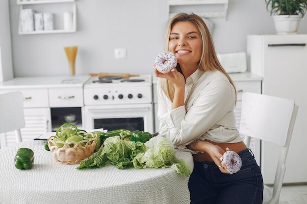 Donna bella e sportiva in una cucina con verdure