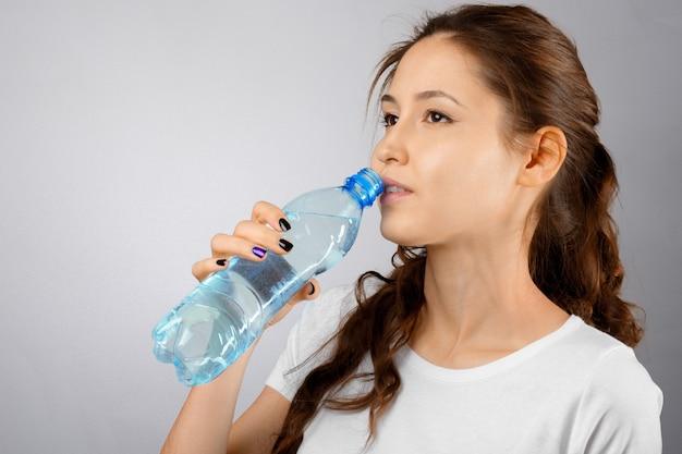Donna bella giovane fitness con perfetta forma del corpo che beve acqua dolce