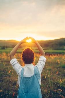 Donna bella giovane hipster a forma di cuore che gode del tramonto sul picco della montagna