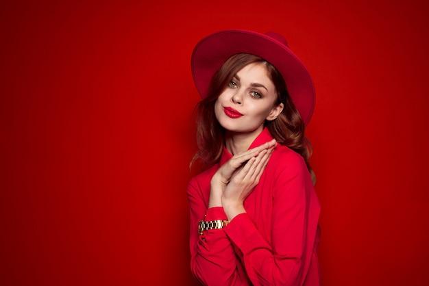 Donna bella moda in un cappello rosso con rossetto rosso sulle labbra