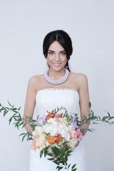 Donna bella sposa in abito da sposa che tiene un mazzo di fiori