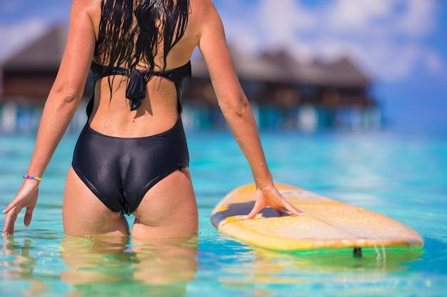 Donna bella surfista fitness praticando il surfing durante le vacanze estive