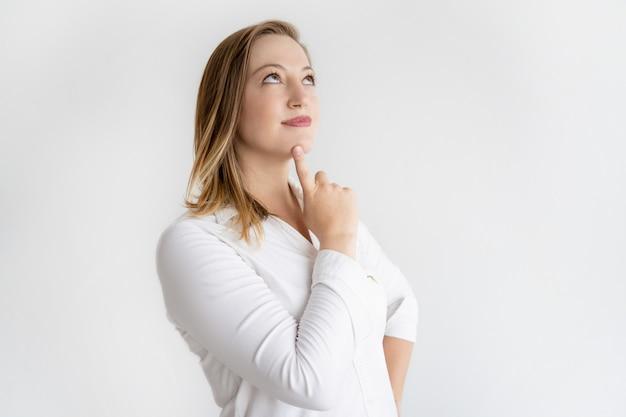Donna bella vaga che tocca il mento con il dito