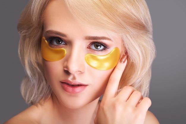 Donna bellezza viso con maschera sotto gli occhi.