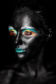 Donna bellissima modella con creativo maschera in plastica nera insolita brillante trucco colorato con la faccia nera