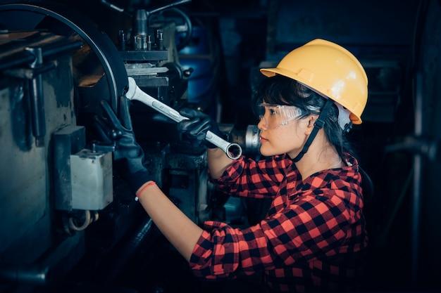 Donna beuatiful asiatica che lavora con la macchina nell'ingegnere della fabbrica e concetto della donna lavoratrice o giorno della donna