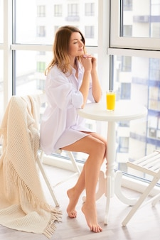 Donna bianca pensierosa a casa che beve il succo di arancia fresco alla mattina in salone