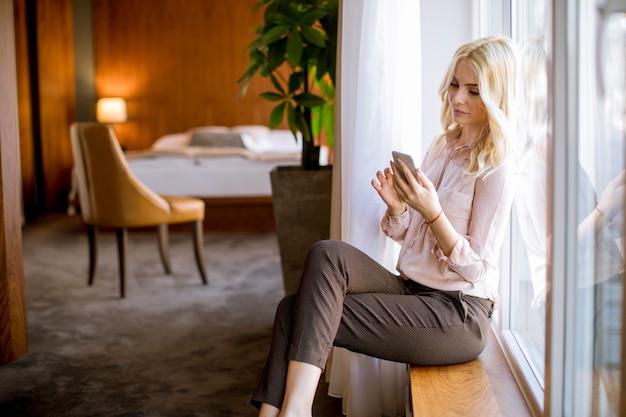 Donna bionda abbastanza giovane con il telefono cellulare dalla finestra nella stanza