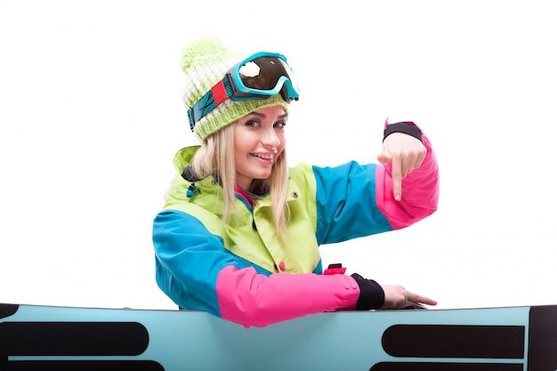 Donna bionda abbastanza giovane in vestito variopinto della neve che si siede a gambe accavallate dietro lo snowboard
