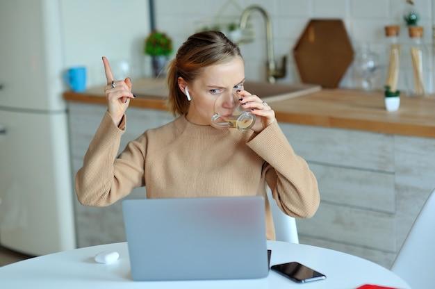 Donna bionda adorabile che lavora con il suo computer portatile mentre sedendosi nella cucina nel suo appartamento