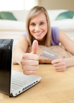 Donna bionda allegra che compera online che si trova sul pavimento