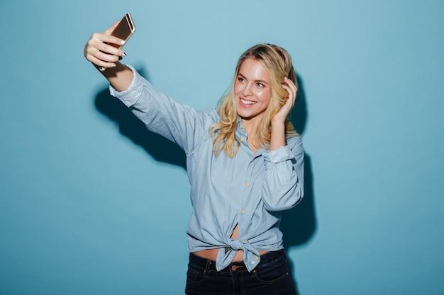 Donna bionda allegra in camicia che fa selfie sullo smartphone