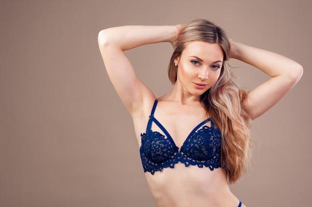 Donna bionda attraente che posa in biancheria alla moda in studio