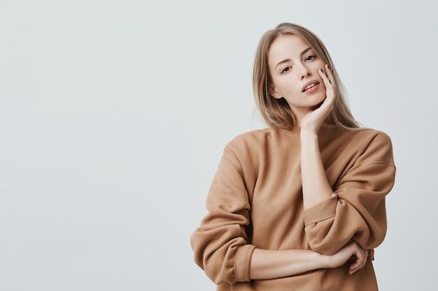 Donna bionda attraente dall'aspetto piacevole vestita in maglione sciolto beige con accattivanti occhi scuri e labbra divise