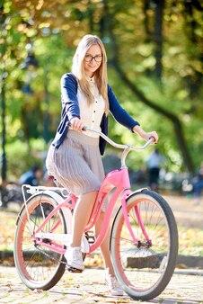 Donna bionda attraente felice sorridente dei giovani che cicla la bicicletta rosa di signora lungo il vicolo pavimentato soleggiato del parco sul fogliame verde giallo dorato vago del bokeh