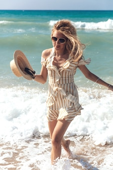 Donna bionda attraente in vestito a strisce agghiacciante sul mare