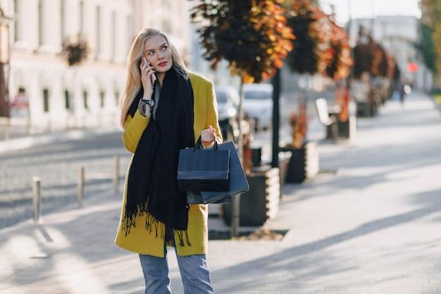 Donna bionda attraente sveglia con i pacchetti sulla via in tempo soleggiato. comunica al telefono dopo lo shopping, emozioni positive.
