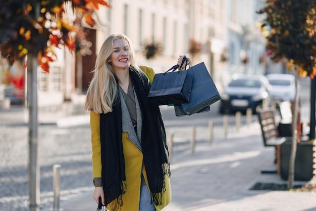 Donna bionda attraente sveglia con i pacchetti sulla via in tempo soleggiato. shopping ed emozioni positive.