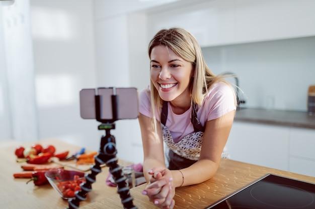 Donna bionda caucasica attraente sorridente in grembiule chinandosi sul bancone della cucina e guardando la ricetta su smart phone. sul bancone della cucina ci sono le verdure.