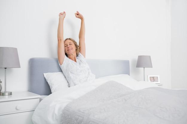 Donna bionda che allunga le braccia a letto la mattina
