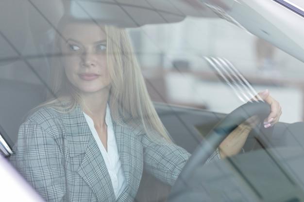 Donna bionda che guida con attenzione la macchina