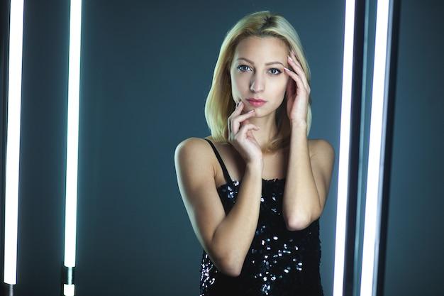Donna bionda che indossa abito elegante cami cinturino in paillettes nero in piedi su interni scuri