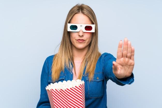 Donna bionda che mangia i popcorn che fanno gesto di arresto con la sua mano