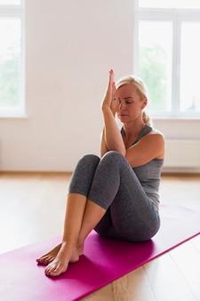 Donna bionda che medita in abiti sportivi