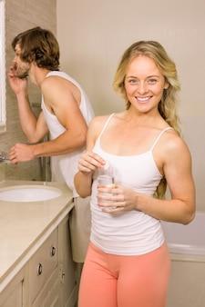 Donna bionda che prende una pillola con il suo ragazzo che pulisce i suoi denti nel bagno a casa