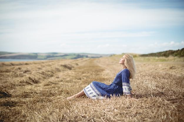 Donna bionda che si siede nel campo
