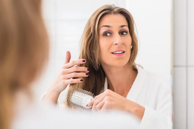 Donna bionda che si spazzola i capelli