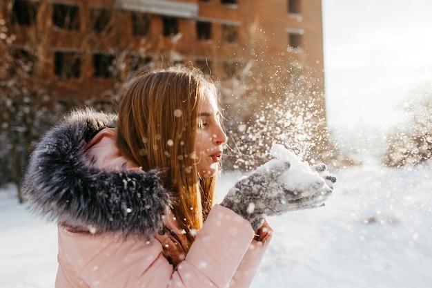Donna bionda che soffia neve dalle mani